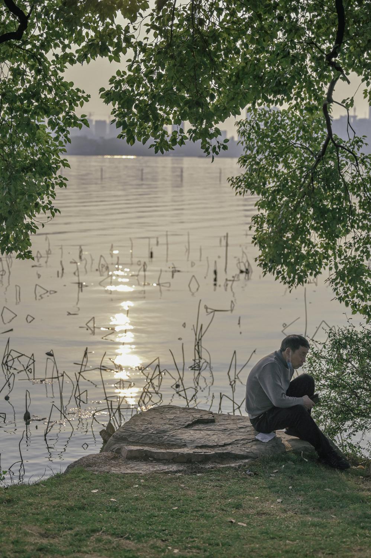 夕阳下,湖边的中年人。