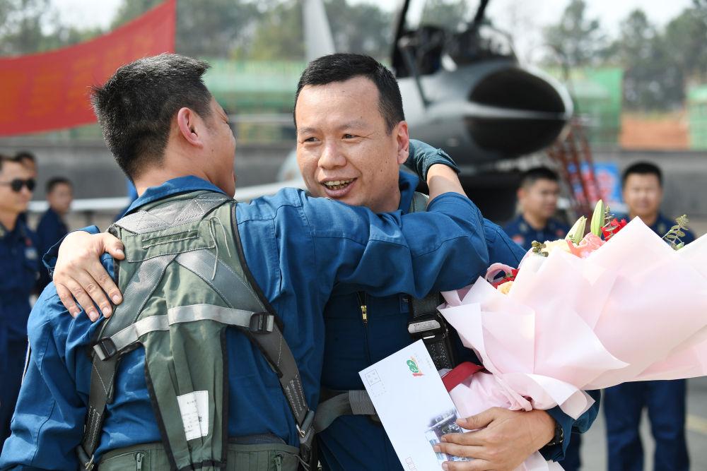 2月23日,复飞重返战位的一等功空军飞行员王建东完成飞行计划后,与战友拥抱庆祝。 唐俊 摄