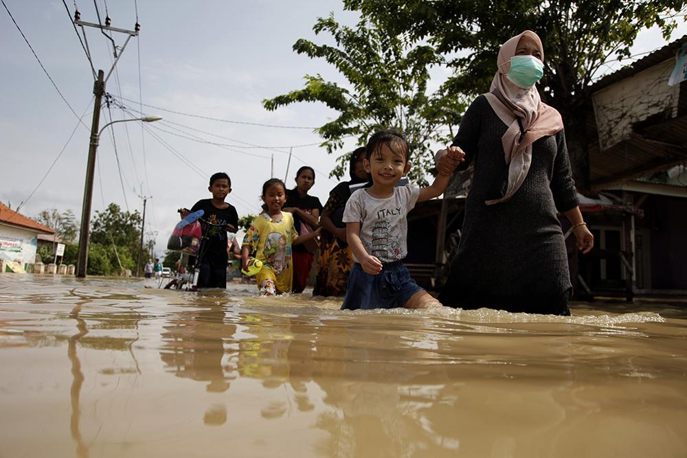 当地时间2021年2月22日,印度尼西亚勿加泗,当地遭遇暴雨引发洪涝灾害,市民在水中撤离。