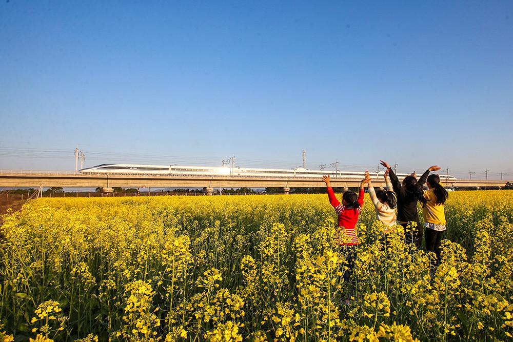 2021年2月20日,在江西吉安峡江县水边镇义桥村,几位小朋友向飞驰而过的昌赣高铁动车挥手。