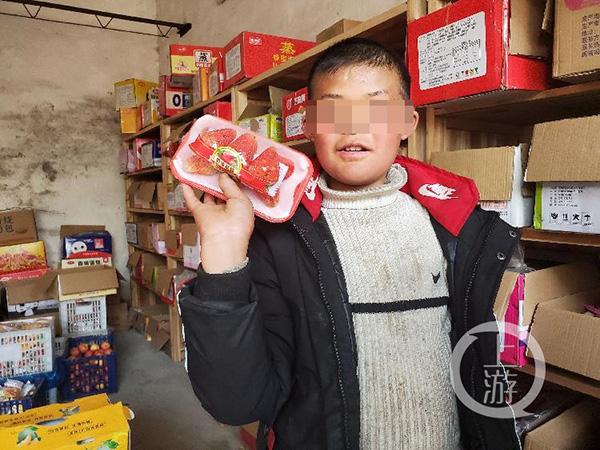 2月24日,永丰县石马镇严辉村,范小勤的哥哥范小勇在村中小卖部挑选水果。