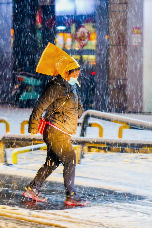 2021年2月24日晚,郑州,一位忘带雨具的市民冒雪出行。