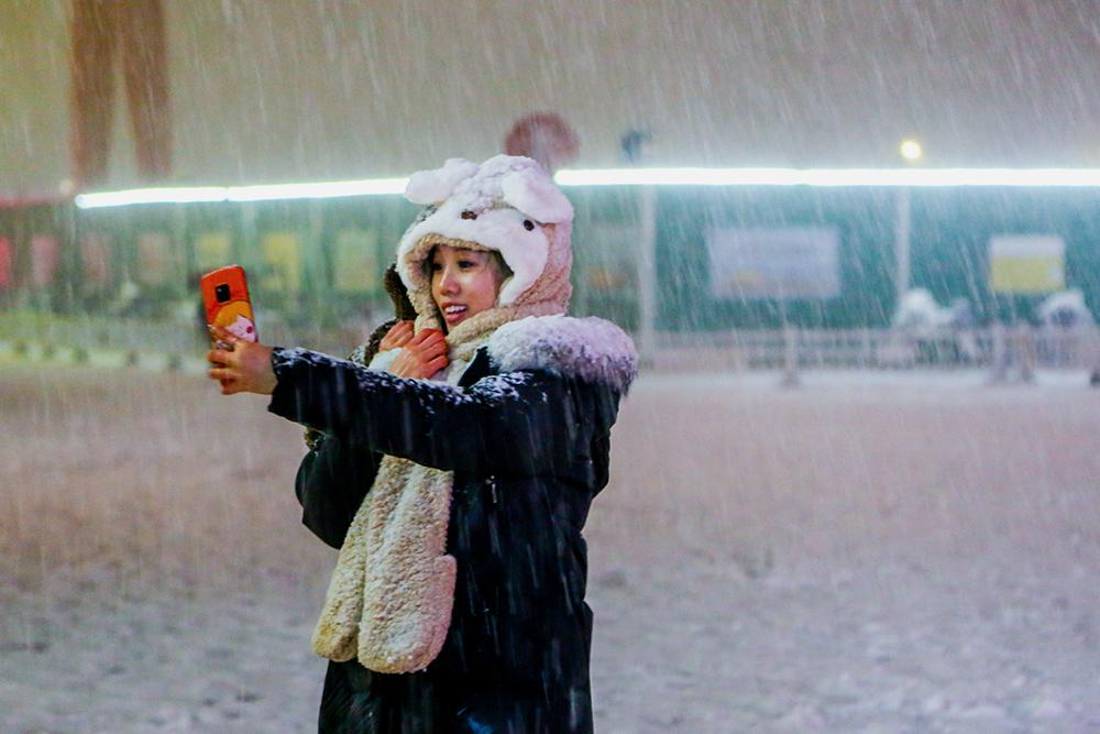 2021年2月24日晚10时许,郑州,市区地上已经是雪白一片,很多市民不顾雷电的威胁,直接出门踏雪。
