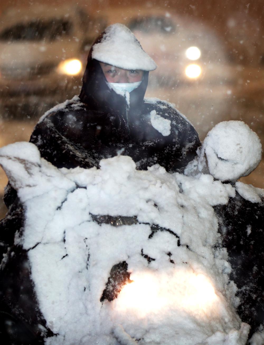 2021年2月24日晚,郑州市民冒雪出行,雨披上的积雪能看出雪有多大。