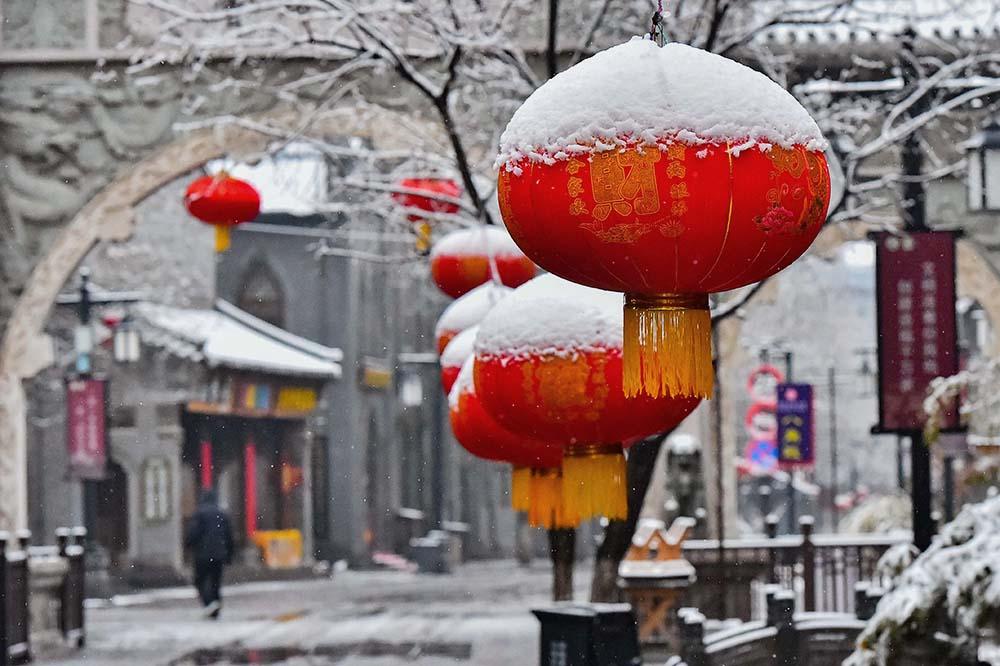 2021年2月25日,山东潍坊青州市,街头的红灯笼被雪覆盖,仿佛戴了顶白帽,甚是可爱。