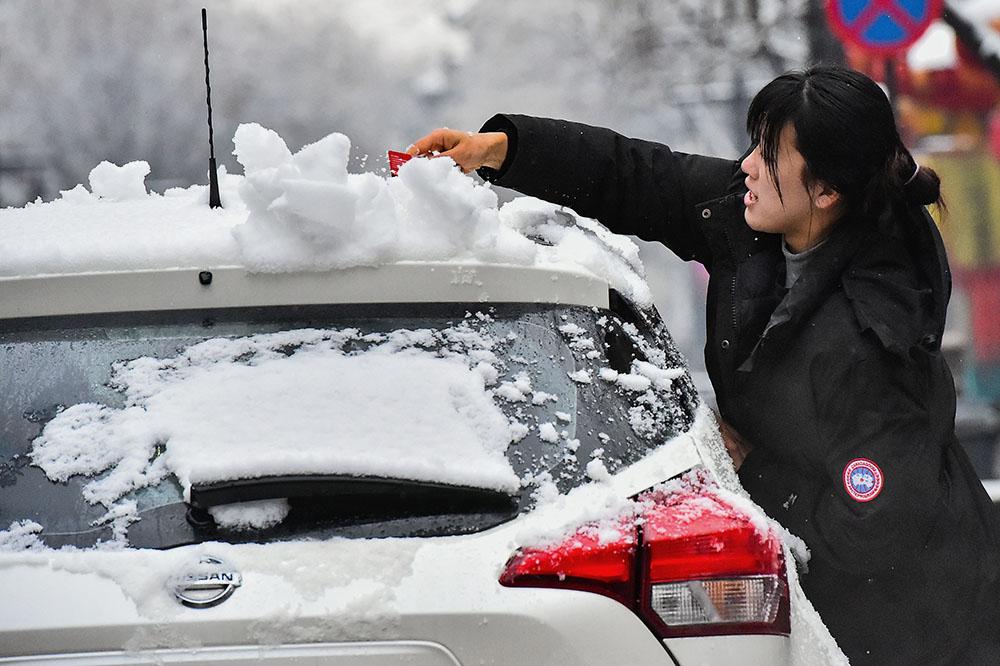 2021年2月25日,山东潍坊青州市,市民在清除车上厚厚的积雪。