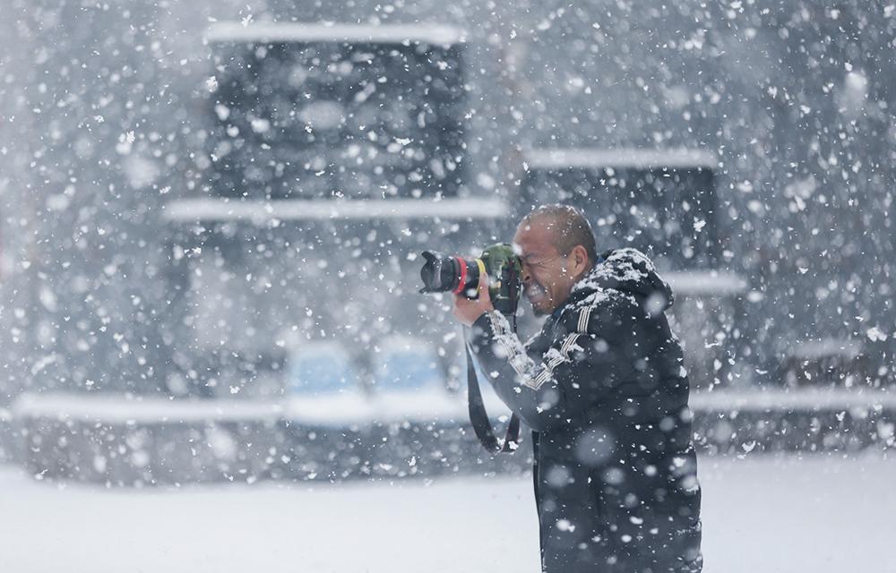 2021年2月24日,山西省运城市稷山县, 摄影师在雪中拍照。