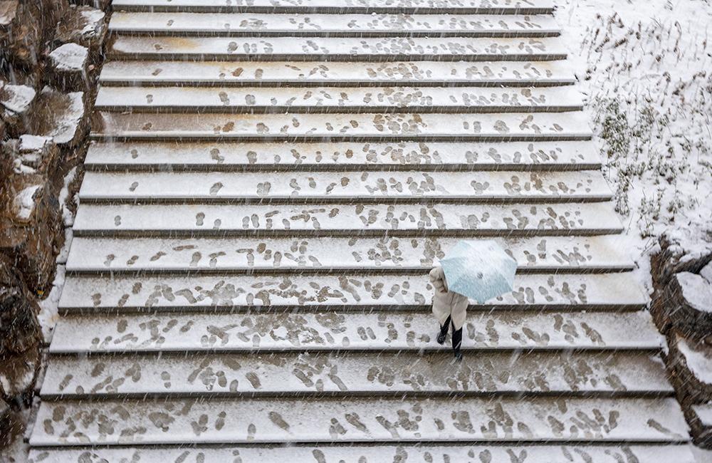 2021年2月24日,山西运城,瑞雪飞飞扬扬,漫山遍野银装素裹,一处台阶上的脚印和雪中行走的市民相映成趣。