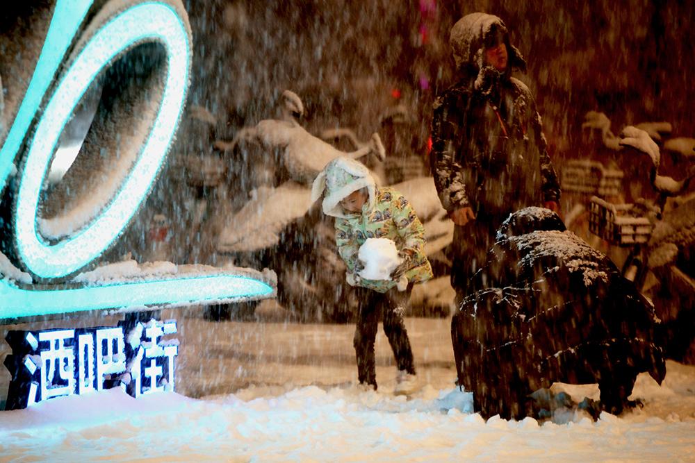 2021年2月24日夜,郑州,家长带着孩子在雪中玩耍。