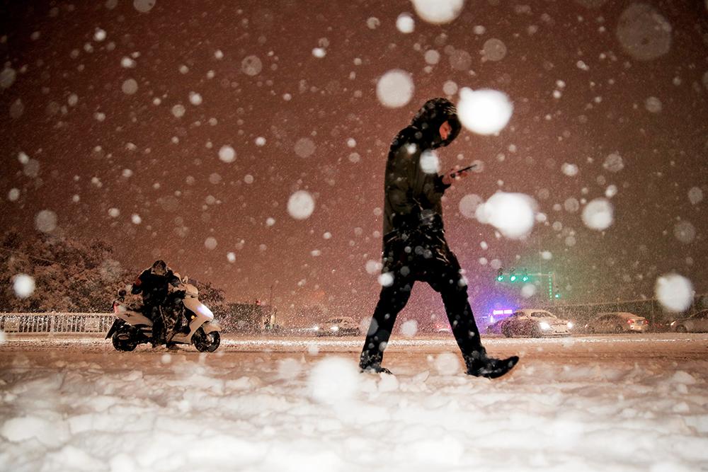 2021年2月25日凌晨,郑州,市民冒雪出行。