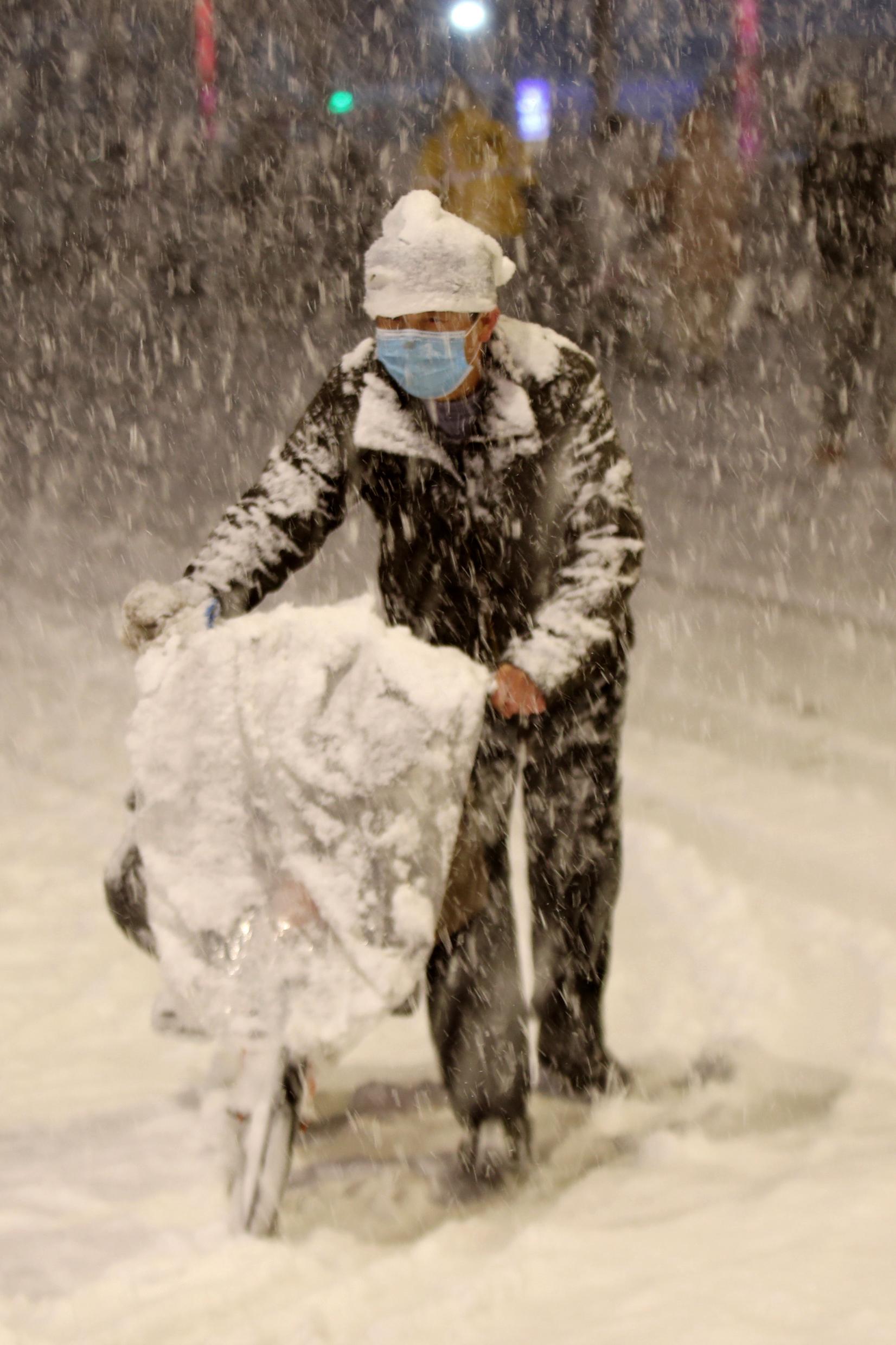 2021年2月24日晚,银装素裹的郑州城区,市民推着车冒雪出行。