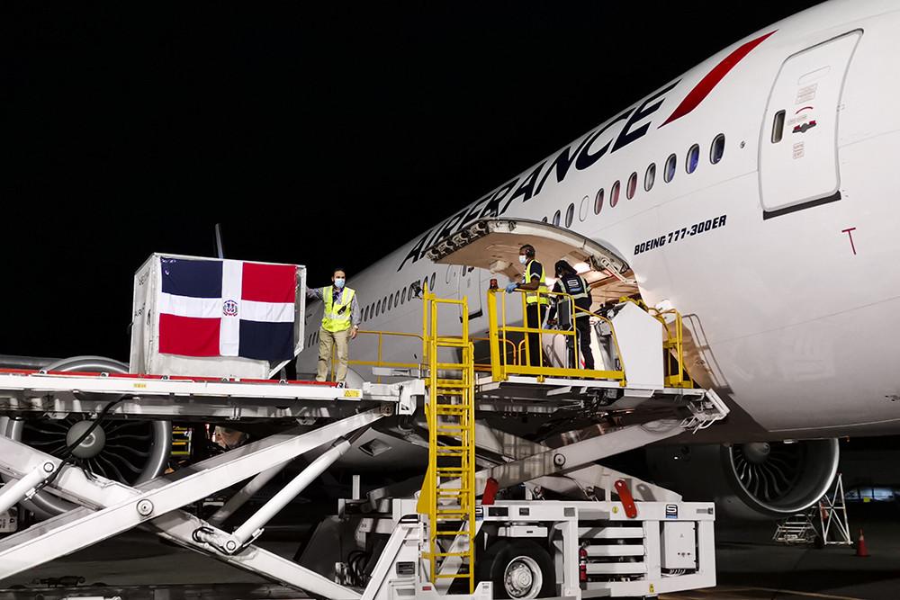2021年2月23日,在多米尼加首都圣多明各国际机场,工作人员从飞机上卸下装有中国科兴新冠疫苗的温控集装箱。