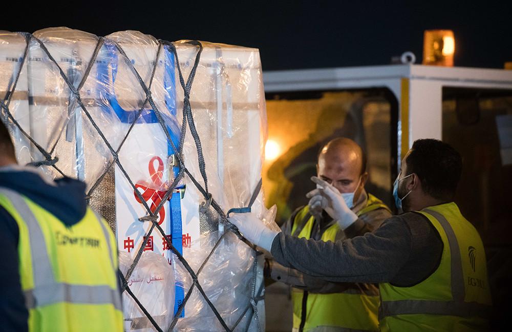 2021年2月23日,在埃及开罗国际机场,工作人员运输中国援助的疫苗。