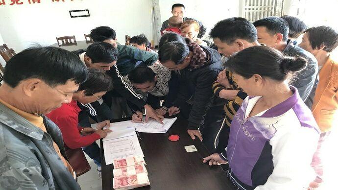 图为 2021年春节前夕,隆道村养殖合作社给村民分红