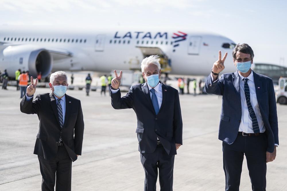 """2021年2月25日,智利总统皮涅拉(中)、卫生部长帕里斯(左)和科技部长顾夫在运送中国科兴疫苗的飞机前摆出""""V""""字手势。""""V""""是疫苗的西语单词的首字母,在智利疫苗接种宣传活动中,人们用""""V""""字手势表达""""我接种疫苗""""之意。"""