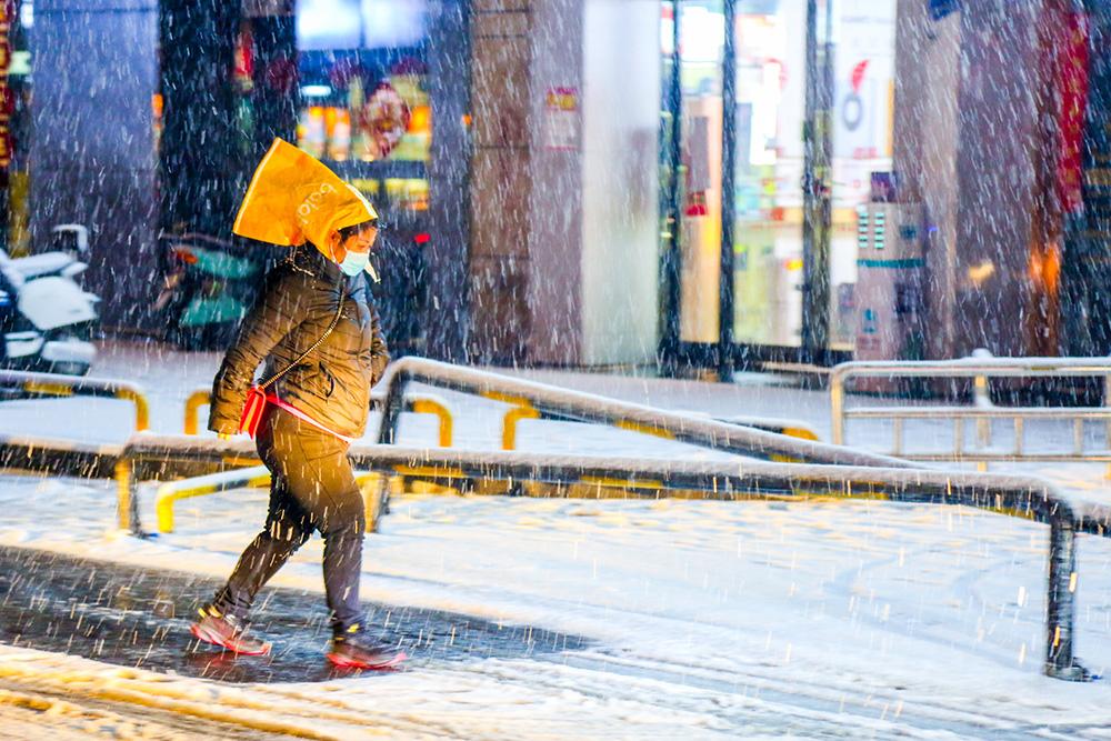 2021年2月24日晚,一位忘带雨具的女士冒雪出行。当日,河南发布暴雪黄色预警,郑州迎来了牛年首场大雪。鹅毛雪花洋洋洒洒从空中落下,迅速在地面形成超10厘米厚的积雪,同时还伴有闪电和雷声。IC 图