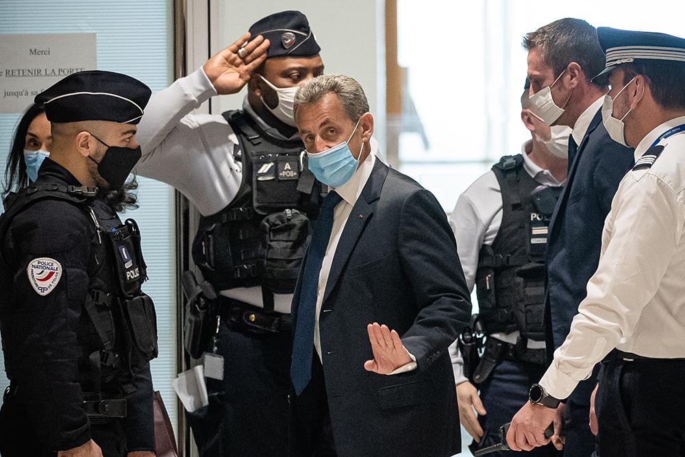 """当地时间2021年3月1日,法国前总统萨科齐(中)抵达巴黎一家法院。据法国媒体1日报道,法国巴黎轻罪法院当天裁定前总统萨科齐""""腐败""""和""""以权谋私""""罪名成立,判处其3年有期徒刑,其中包括1年实刑。"""