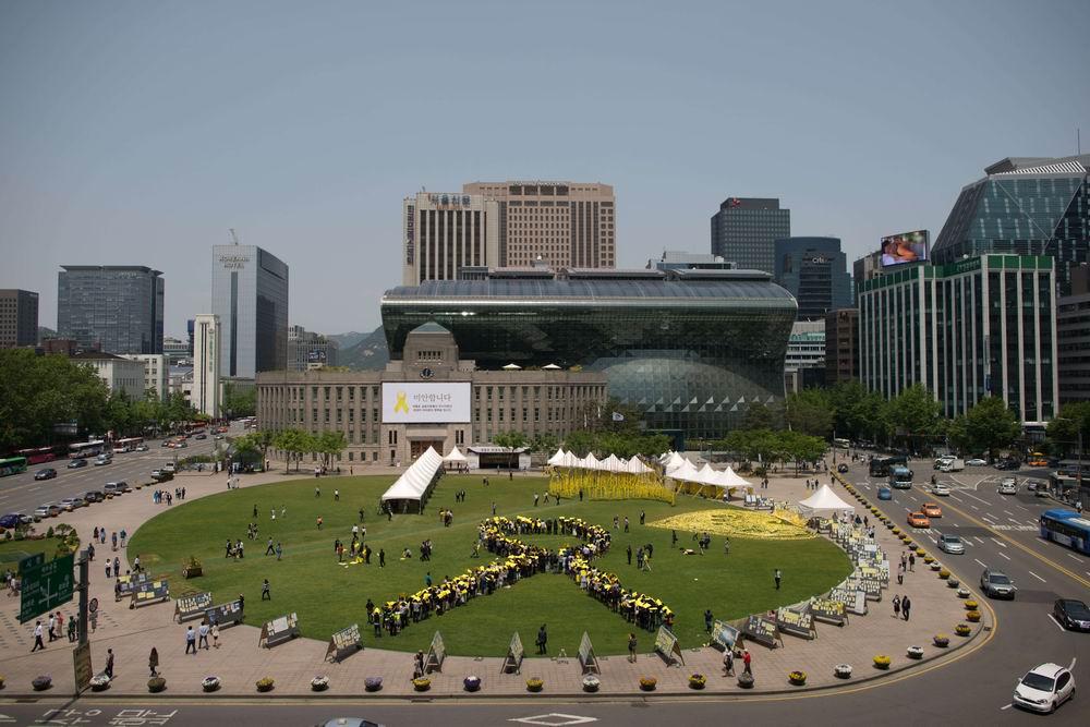 2014年5月16日,韩国首尔市政府前广场,民众摆出巨大黄丝带造型,追思沉船事故遇难者与失踪者。