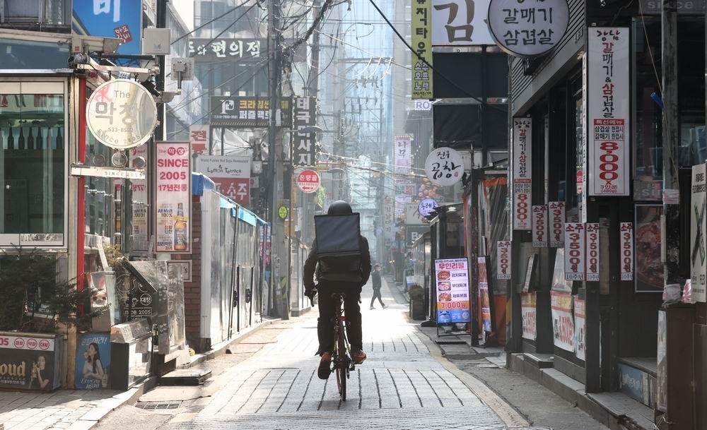 2020年12月24日,韩国首尔,送餐的外卖员骑车经过首尔江南站附近的饭店。