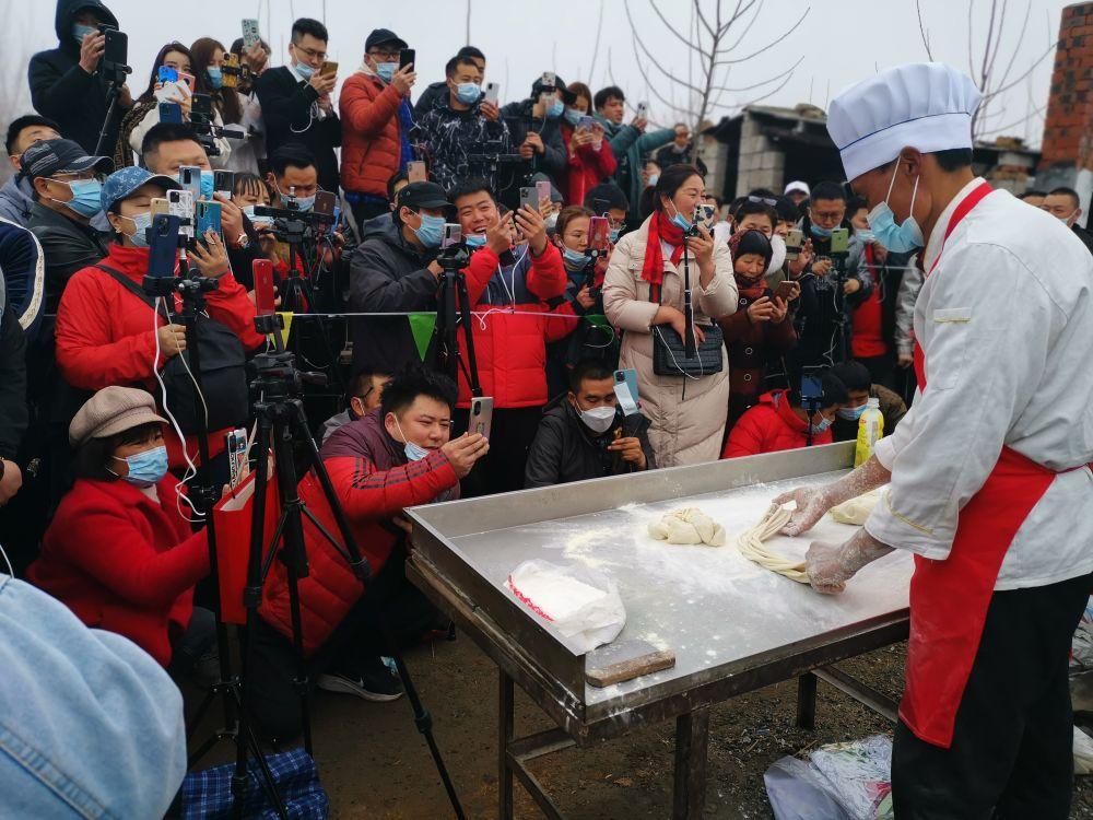 2月28日,众多网红和视频博主将费县梁邱东大集上程运付的拉面摊围得水泄不通。新华社记者贾云鹏摄