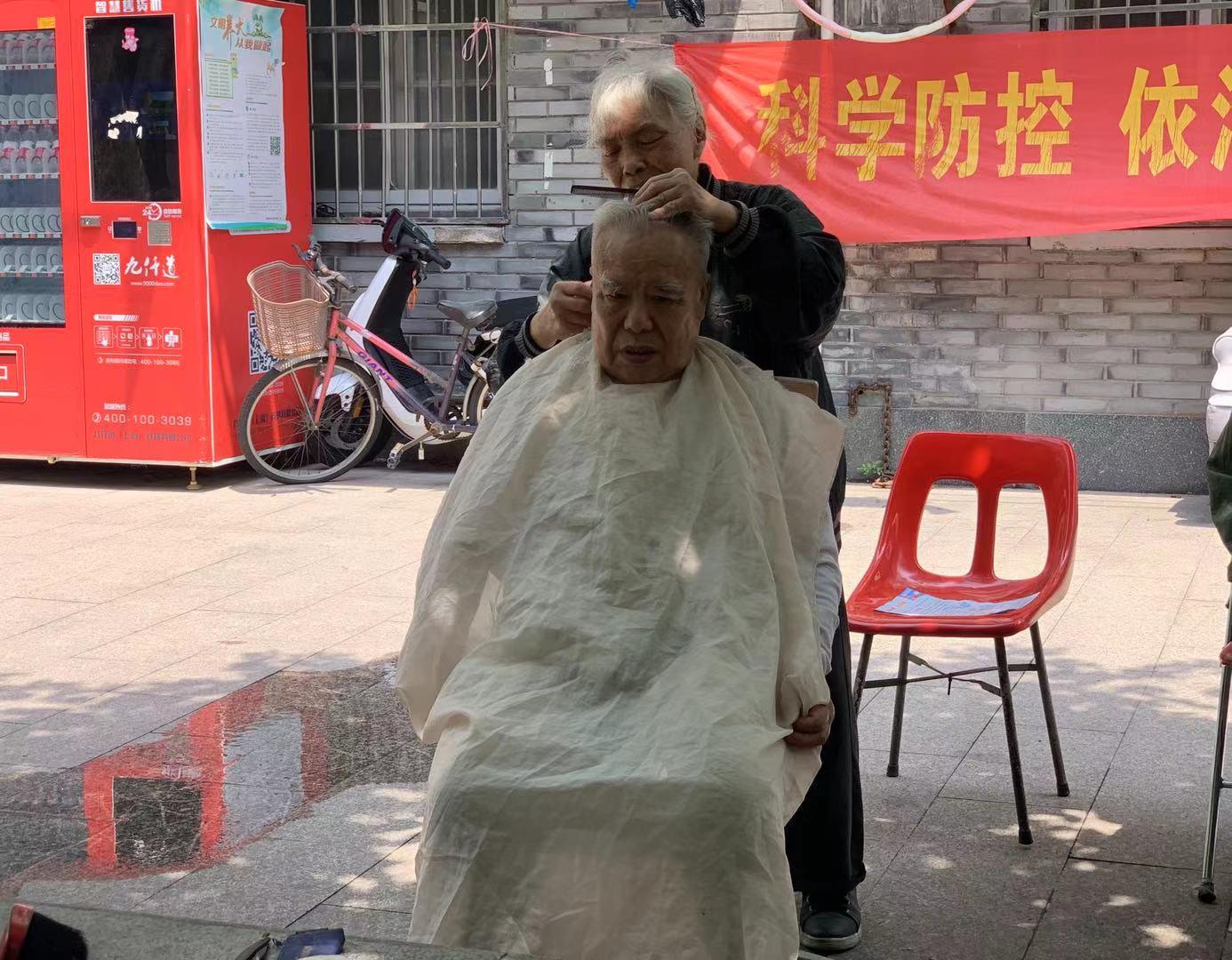 金淑华在社区老年活动室门口为老人理发。友谊社区供图