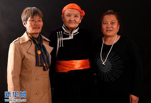 都贵玛(中)、她的女儿旭日(右)和前来探望她们的斯日巴勒合影。斯日巴勒是都贵玛曾经抚养过的子女之一。 图片来自新华网