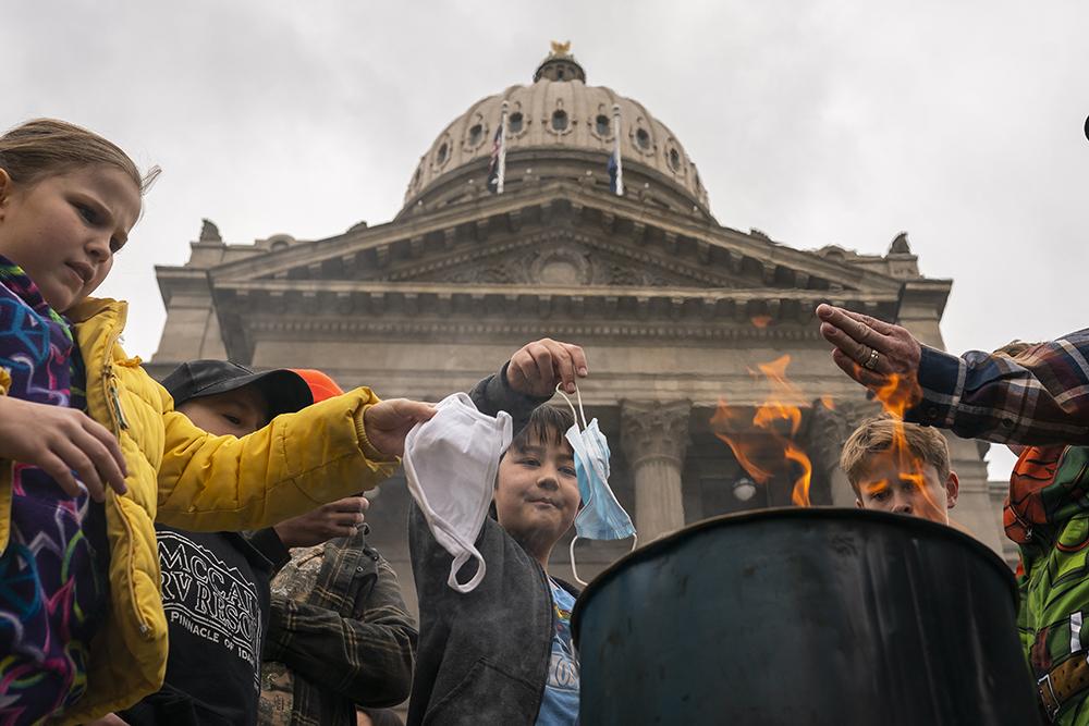 """当地时间2021年3月6日,美国爱达荷州首府博伊西,当地发生针对口罩令的抗议示威事件,现场有超过百名的民众聚集在州议会大厦外焚烧口罩。参加抗议示威的民众还在州议会大厦外悬挂写有""""焚烧口罩""""和""""让爱达荷州自由""""字样的标语。在现场,成年人还鼓励前往现场的孩子们一同焚烧口罩。"""
