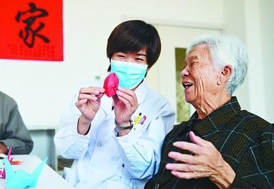 河北沧州青县康泰养老护理中心护理人员与老年人一起折纸。新华社发