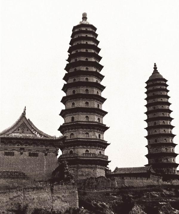 山西太原府永祚寺的双塔。两座叠层塔高54米,塔院的轴线为东南—西北走向。建于1611年,倾斜的塔心建造时间可能更晚些。左侧是永乐寺的宏伟大殿。伯施曼拍摄。