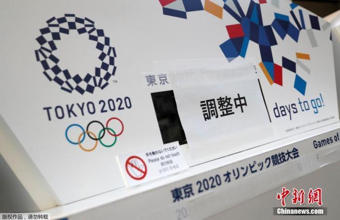 """资料图:2020年3月25日,由于东京奥运会被宣布延迟举办,东京市内一处倒计时电子屏停止工作,并被贴上了""""正在调整""""的标签。"""