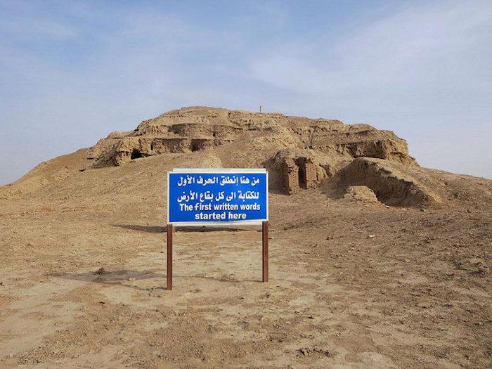 """乌鲁克遗址现状(2016年),位于现伊拉克境内塞马沃以东40公里处。蓝色告示板上的阿拉伯语标语写着""""最早的书写从这里开始,传播到世界各地""""。"""