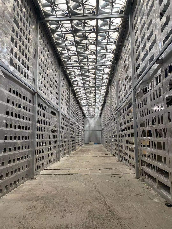 当前空荡荡的厂房内部,两侧是剪开的矿机散热孔