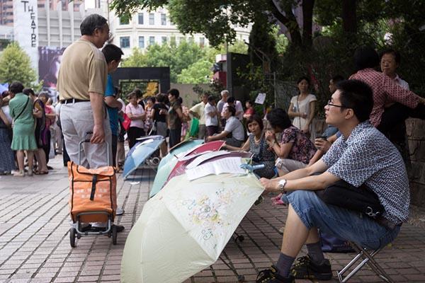 2014年8月31日,上海人民公园相亲角,家长浏览雨伞上的征婚信息。 澎湃新闻资料图 贾亚男