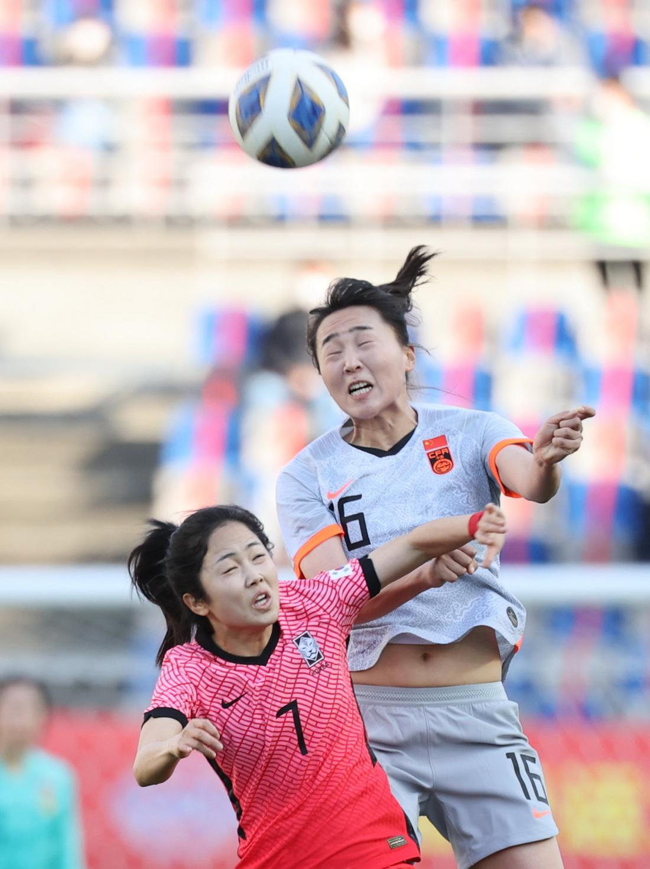 中国女足队员王晓雪(16号)与韩国女足队员李玟娥(7号)在场上拼抢
