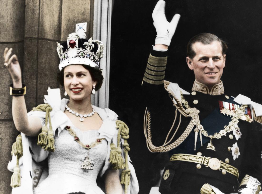 当地时间1953年6月2日,英国伦敦,女王加冕礼当日,英国女王伊丽莎白二世与丈夫菲利普亲王在白金汉宫向民众挥手致意。在加冕典礼上,菲利普宣誓效忠,成为第一个向新女王下跪的臣民。