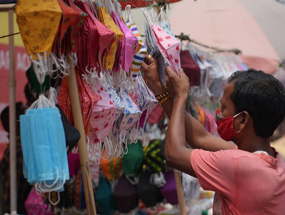 当地时间2021年4月8日,印度民众在特里普拉邦阿加尔塔拉街头购买口罩。印度卫生部8日报告,印度过去24小时新增新冠确诊病例126789例,不仅刷新印度单日新增确诊病例纪录,也是本周以来印度单日新增病例第三次突破10万例。