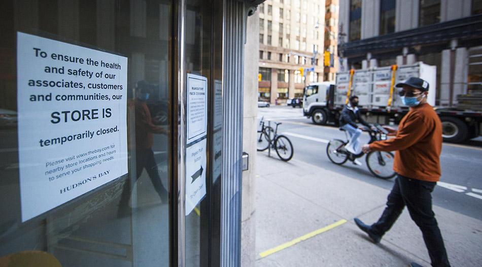 当地时间2021年4月8日,在加拿大安大略省多伦多,一名男子走过一家暂停营业的商店。