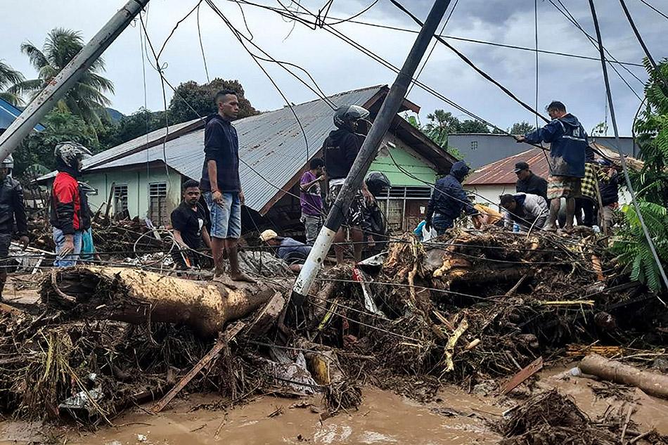 """当地时间2021年4月7日,印度尼西亚东弗洛雷斯,热带气旋""""塞罗亚""""带来暴雨,居民检查被毁房屋附近的废墟。印度尼西亚国家抗灾署8日通报,印尼日前由热带气旋带来的极端天气已导致165人死亡、45人失踪,目前已有2万多灾民被紧急撤离。印尼政府出动7500多名军警参与撤离和搜救行动。4月4日过境东努沙登加拉省的热带气旋""""塞罗亚""""带来的暴雨引发洪水、泥石流、山体滑坡等灾害。除了人员伤亡,还有115座公共设施和13600多所房屋遭到不同程度的损坏。"""