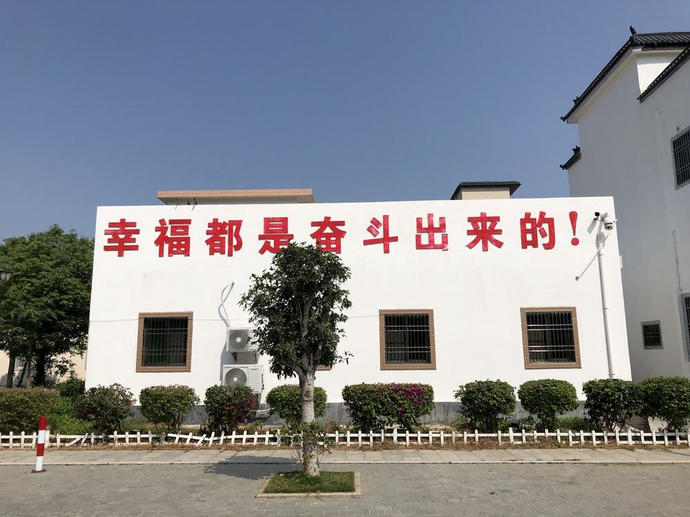 """新山村重视党建工作,村内打出了""""幸福都是奋斗出来的""""的标语。"""