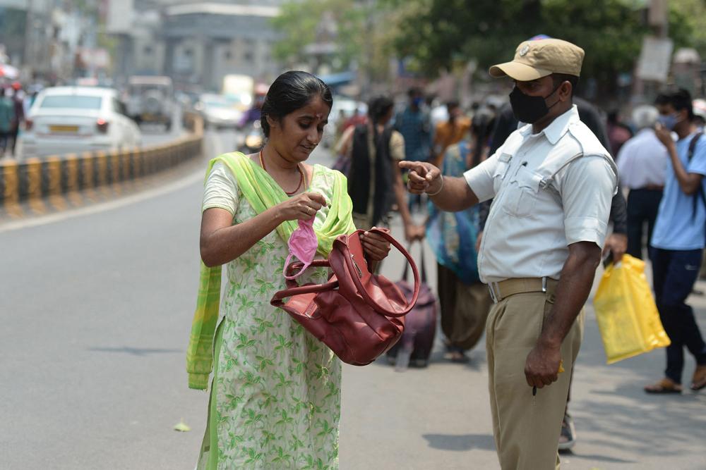 当地时间2021年4月12日,印度海得拉巴,警察在街头督促民众佩戴口罩,以防止新冠疫情的蔓延。