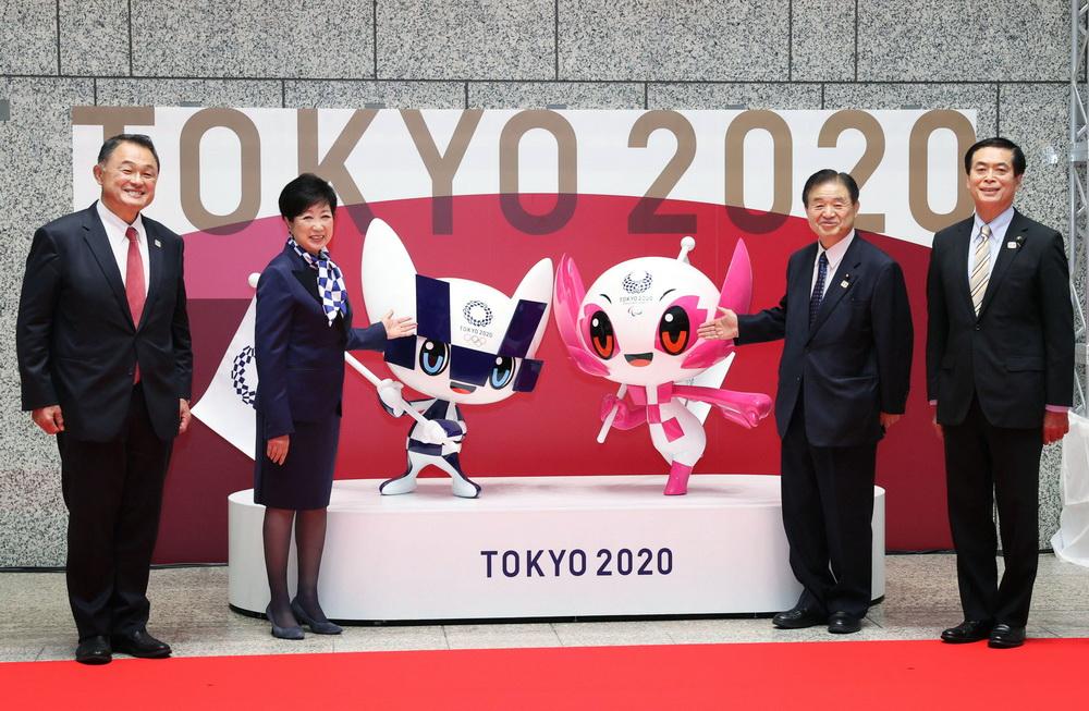 """当地时间2021年4月14日,日本东京,东京市长小池百合子、日本奥委会主席山下康弘等人在东京都政府总部合影留念,为迎接东京奥运会开幕倒计时100天。当天还揭晓了残奥会吉祥物:""""Miraitowa""""和""""Someity""""。"""