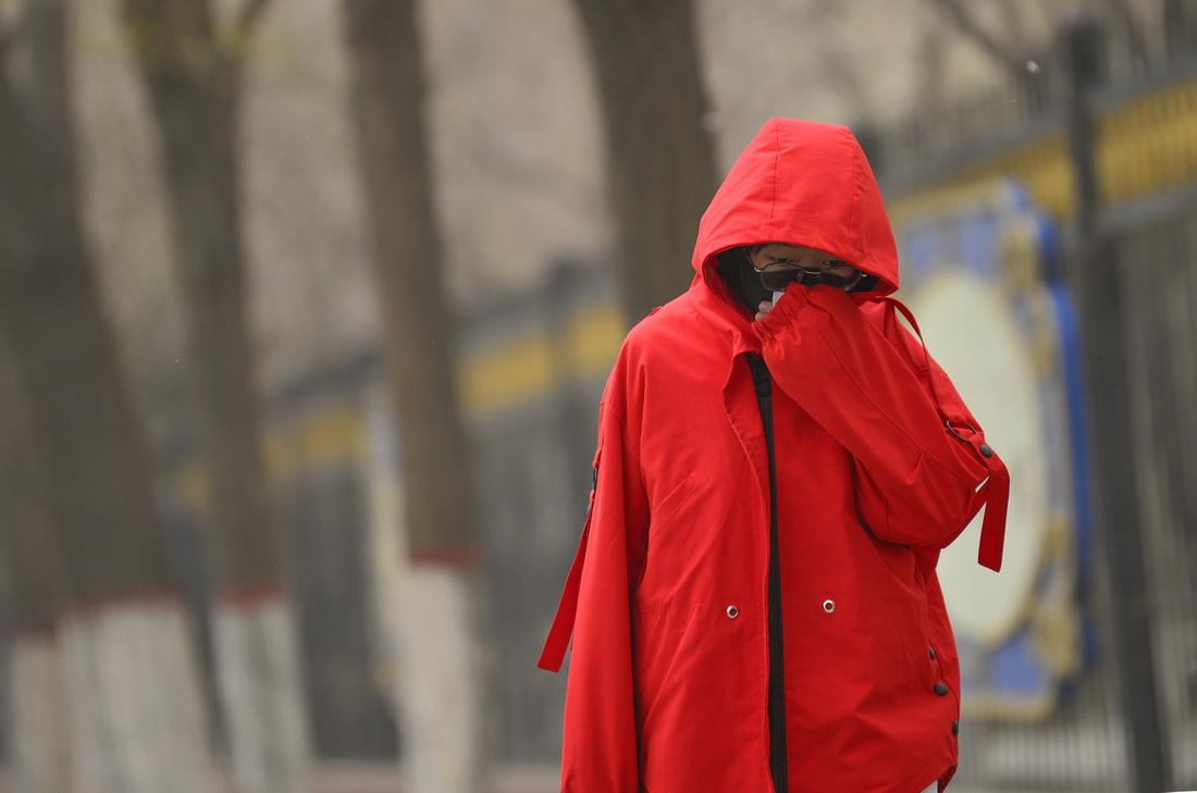 4月15日上午,内蒙古呼和浩特市,市民在沙尘中出行。人民视觉 图
