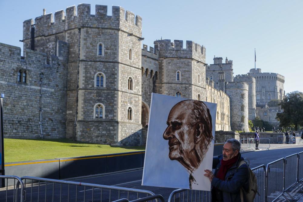 当地时间2021年4月17日,英国伦敦,菲利普亲王葬礼将举行,艺术家Artist Kaya手持菲利普亲王的肖像。