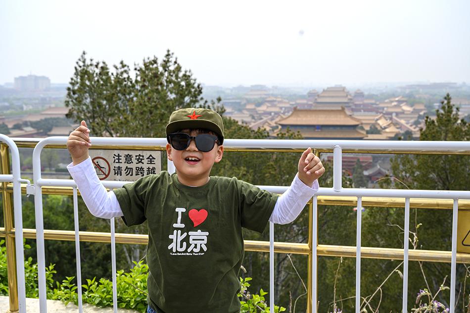 4月11日,北京市景山公园,游客在北京城中心点留影纪念。