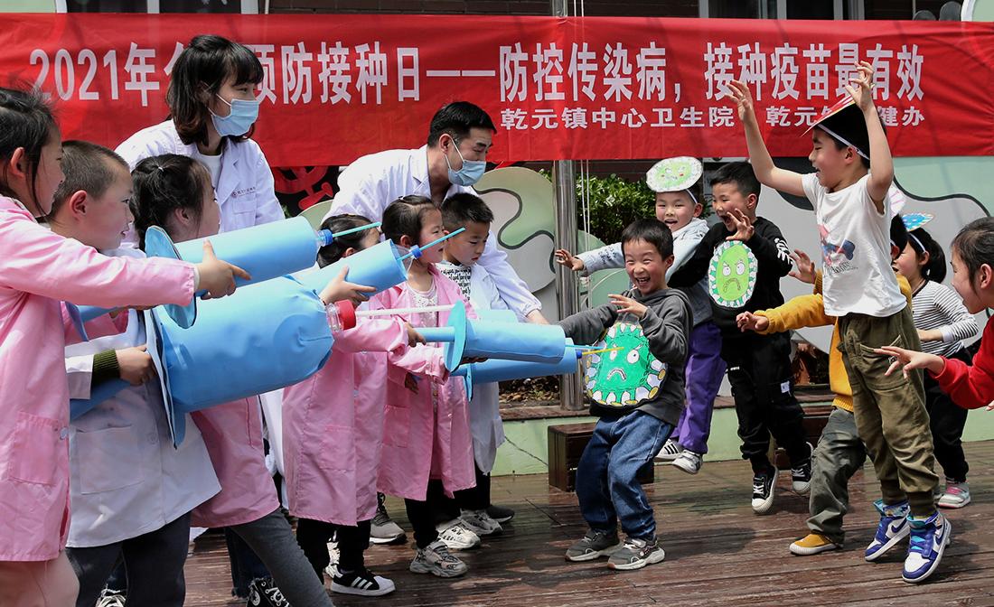 """2021年4月16日,浙江湖州德清县中心幼儿园,乾元镇中心卫生院工作人员用自制的针筒、病毒模型等,和孩子们一起做游戏。为迎接4月25日""""全国预防接种日""""的到来,德清县中心幼儿园在寓教于乐中让孩子们了解新冠病毒、预防接种的重要性。今年全国预防接种日主题是""""防控传染病,接种疫苗最有效""""。倪立芳/人民视觉 图"""