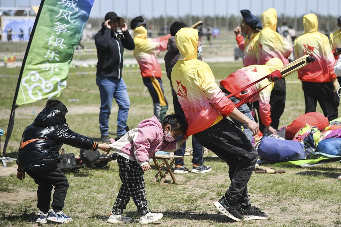 """2021年4月17日,参赛选手在比赛现场放飞风筝,孩子们助选手""""一臂之力""""。当日,第38届潍坊国际风筝会放飞比赛在山东潍坊滨海国际风筝放飞场举行,来自全国各地的多支风筝放飞队参加比赛。 朱峥/新华社 图"""