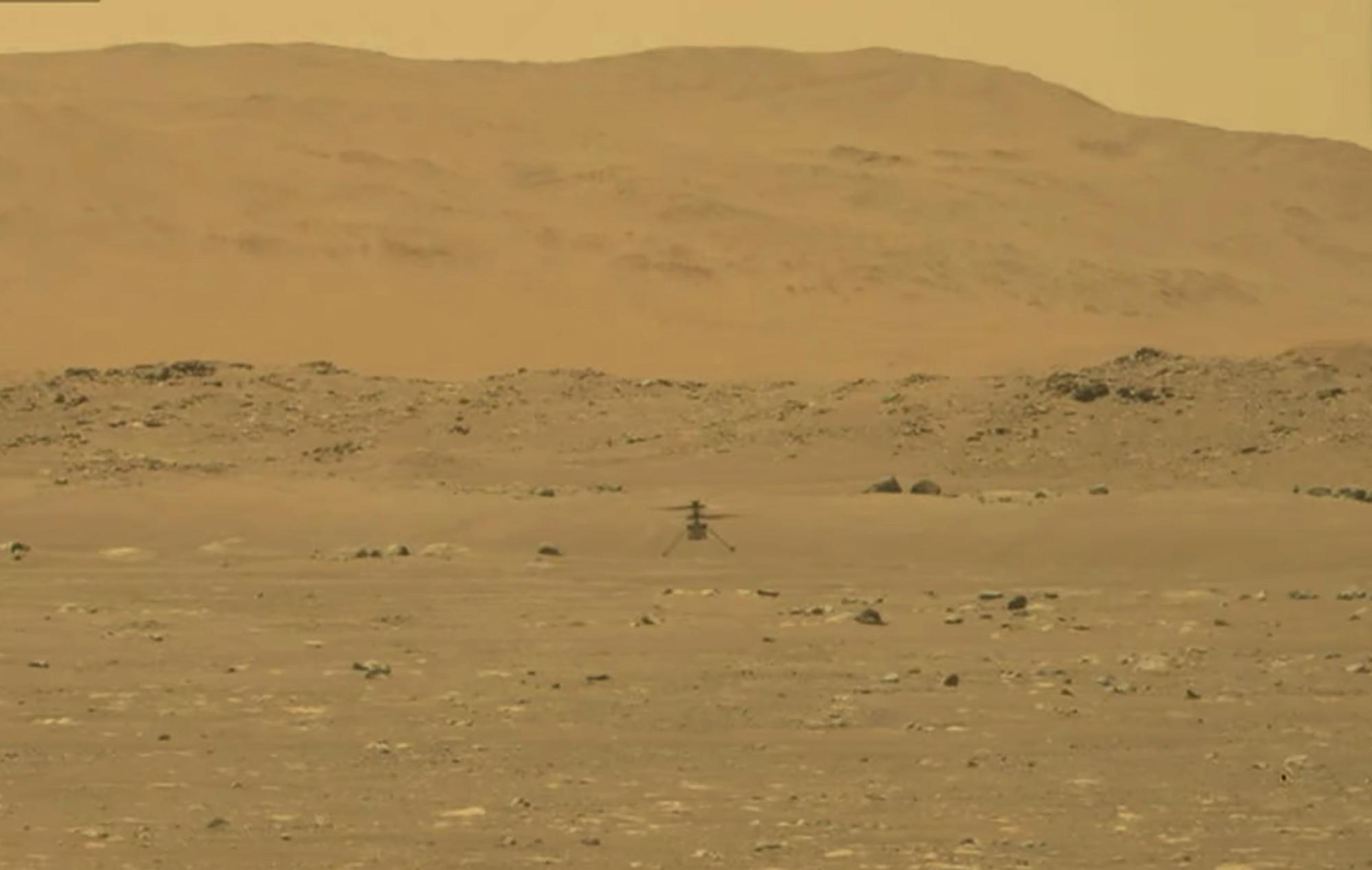 """""""毅力号""""火星车传回拍摄的""""机智""""号直升机首飞升空的影像。"""