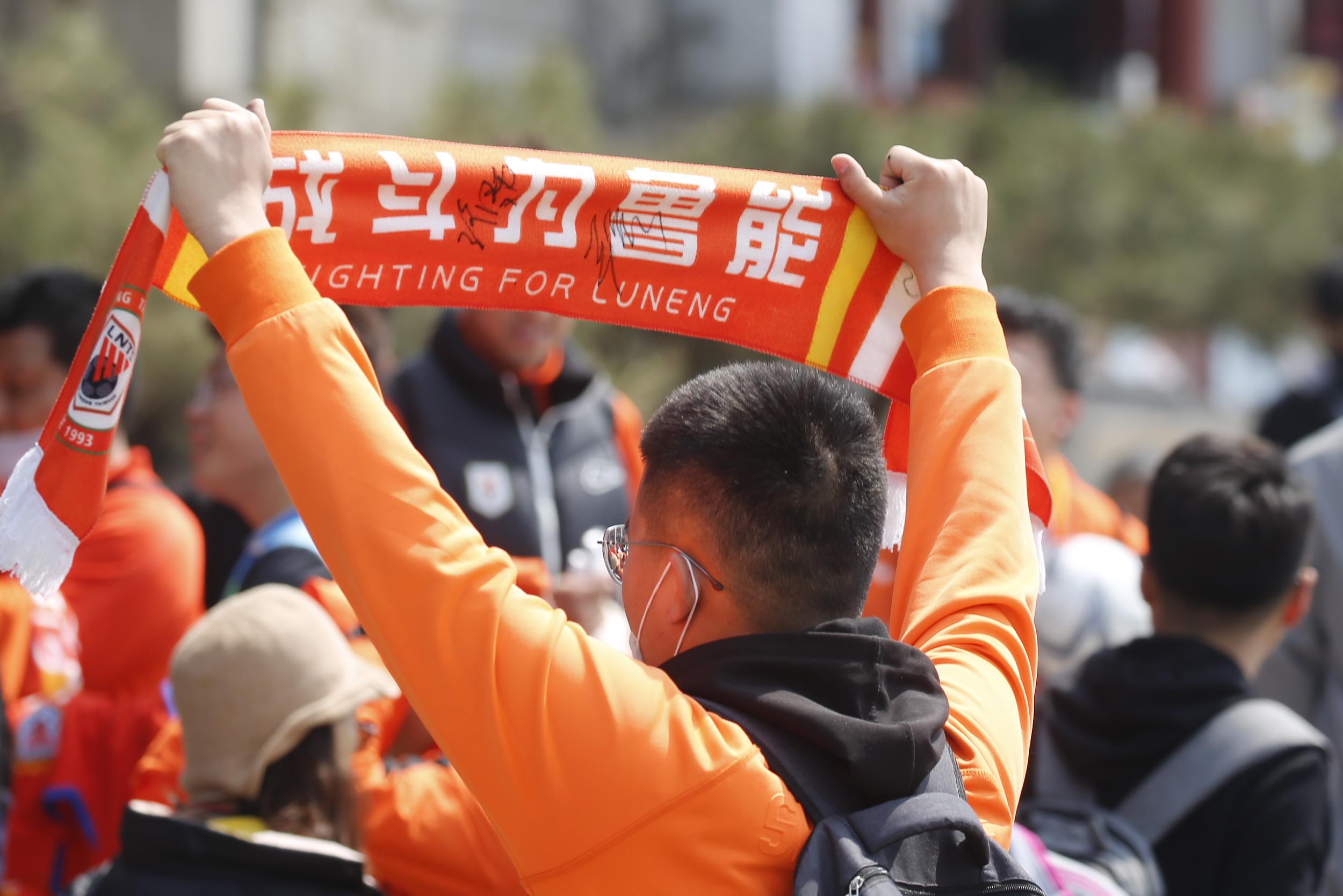 山东球迷手举横幅为球队加油。