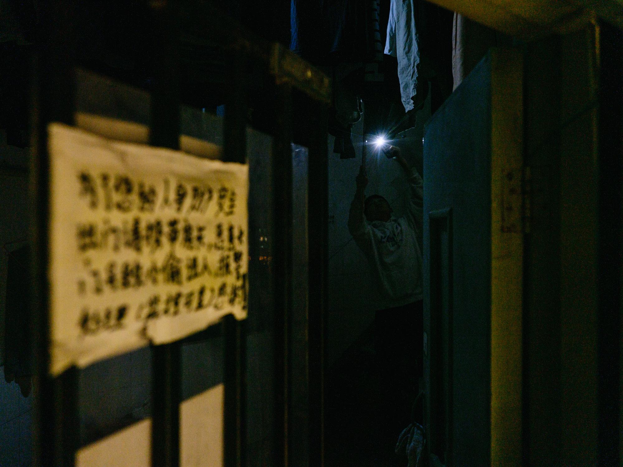 作为消防通道的楼梯是住客唯一能晒衣服的地方。衣物密不透风,不但不易干,挂取也不容易。夜里需要用手机打光仔细翻查,倘若取错再挂回去,又要大费周章。