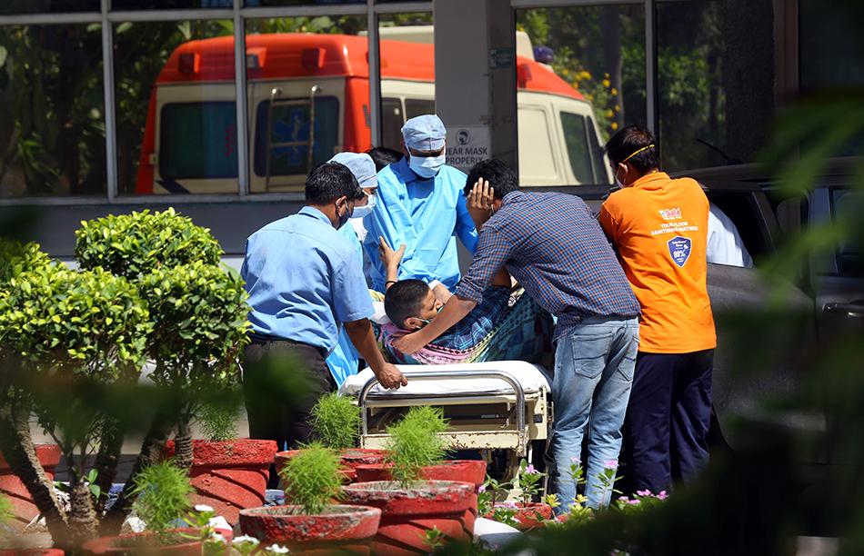 4月24日,人们将新冠患者送入印度新德里一家医院。